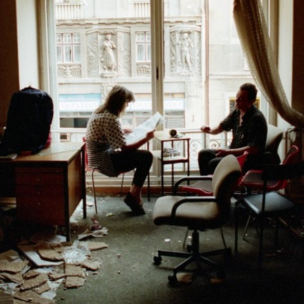 A Bosnian couple reads the newspaper in their bombed-out apartment along Marshal Tito Avenue in Sarajevo.   (Photo by David Turnley/Corbis/VCG via Getty Images)