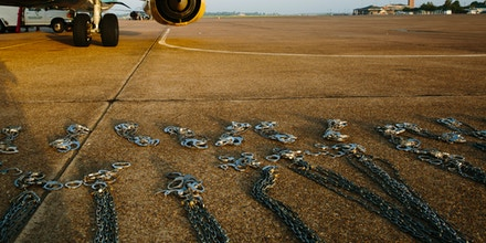 Shackles from a prior Immigration and Customs Enforcement flight (ICE Air) are lined up on the tarmac at Alexandria International Airport in Alexandria, Louisiana before a deportation flight from Alexandria, Louisiana to Guatemala City, Guatemala on August 17, 2017.