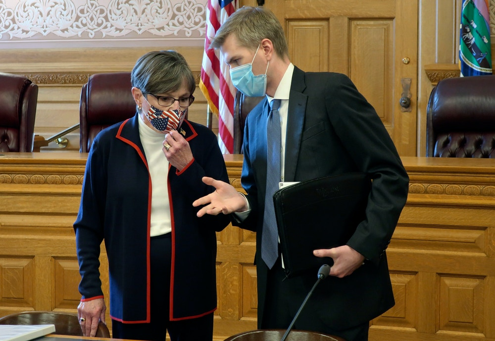 Kansas Gov. Laura Kelly, left, confers with Clay Britton, her chief attorney, before a meeting with legislative leaders about an executive order she issued to require people to wear masks in public, Thursday, July 2, 2020, at the Statehouse in Topeka, Kan. Kelly says she's worried that if the state doesn't reverse a recent surge in reported coronavirus cases, the state won't be able to reopen K-12 schools in August. (AP Photo/John Hanna)