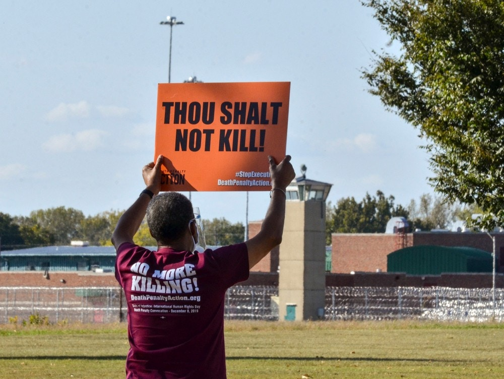 Protester Sylvester Edwards holds a sign up opposing the death penalty from across the street from the federal penitentiary in Terre Haute, Ind., Thursday, Sept. 24, 2020. The U.S. government put, Christopher Vialva, the first Black inmate to death Thursday, since the Trump administration this year resumed federal executions after a nearly two-decade pause. (Austen Leake/The Tribune-Star via AP)