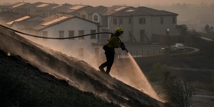 Firefighter Tylor Gilbert puts out hotspots while battling the Silverado Fire, Monday, Oct. 26, 2020, in Irvine, Calif. (AP Photo/Jae C. Hong)