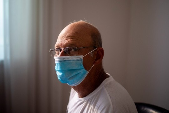 In this photo taken on Sunday, June 28, 2020, former Israeli Air Force general and leading critic of Prime Minister Benjamin Netanyahu, Brig. Gen. Amir Haskel wears a face mask amid the concerns over the country's coronavirus outbreak pose for a photo in Tel Aviv, Israel. After 32 years in the Israeli Air Force, retired Brig. Gen. Amir Haskel wasn't looking to politics. But as his prime minister became further enmeshed in corruption, he felt he could no longer stay silent. So, he picked up a sign and took to the streets in an individual act of protest. Now, after his highly-publicized weekend arrest during a peaceful demonstration, he has become the unquestioned leader of the growing grassroots movement demanding that Benjamin Netanyahu step down. (AP Photo/Ariel Schalit)