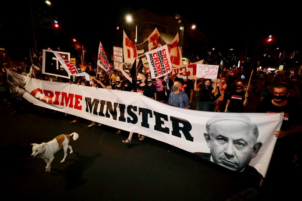 Israeli protesters hold signs and chant slogans during a demonstration against Israeli Prime Minister Benjamin Netanyahu In Tel Aviv, Israel, Thursday, Aug. 27, 2020. (AP Photo/Sebastian Scheiner)