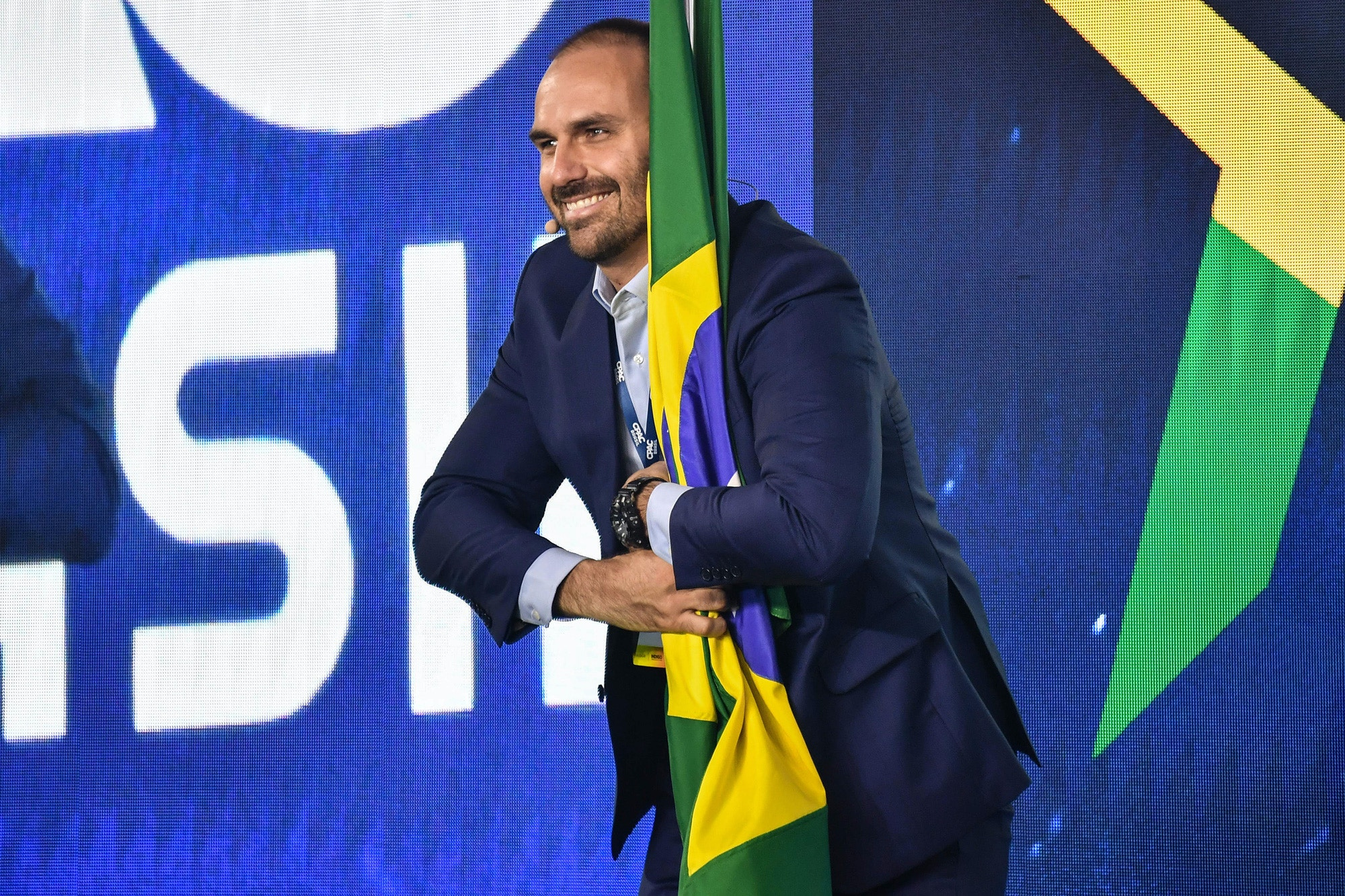 Brazilian Deputy Eduardo Bolsonaro, son of Brazilian President Jair Bolsonaro, holds a Brazilian national flag during the Conservative Political Action Conference (CPAC), in Sao Paulo, Brazil, on October 11, 2019. (Photo by NELSON ALMEIDA / AFP) (Photo by NELSON ALMEIDA/AFP via Getty Images)