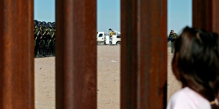 A girl looks through the border fence in Ciudad Juarez, Chihuahua state, Mexico, on January 31, 2020, as U.S. Border Patrol agents conduct a training exercise at the Anapra area, in Sunland Park, New Mexico, US. (Photo by Herika Martinez / AFP) (Photo by HERIKA MARTINEZ/AFP via Getty Images)