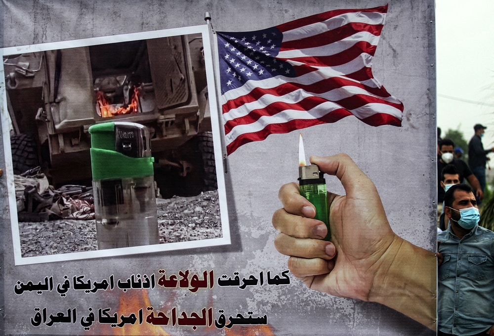 "A sign depicting a hand holding a lighter beneath a US flag and next to a photo of a lighter near a military armoured vehicle with text reading in Arabic ""as the lighter burned the followers of America in Yemen, the lighter will burn America in Iraq"" is seen during a demonstration by supporters of the Iran-backed Hashed al-Shaabi (Popular Mobilisation) paramilitary forces outside the entrance to the Iraqi capital Baghdad's highly-fortified Green Zone on November 7, 2020, demanding the departure of remaining US forces from Iraq. - Several hundred protesters gathered in the Iraqi capital on Saturday afternoon to demand US troops leave the country in accordance with a parliament vote earlier this year. (Photo by Ahmad AL-RUBAYE / AFP) (Photo by AHMAD AL-RUBAYE/AFP via Getty Images)"