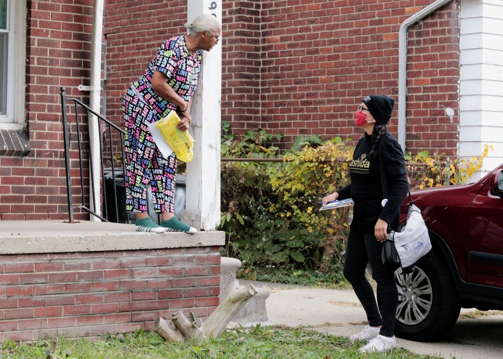 Democratic Rep. Rashida Tlaib encourages a resident to vote in the upcoming presidential elections in Detroit, Michigan, U.S., October 18, 2020.  REUTERS/Rebecca Cook - RC29LJ91STVW