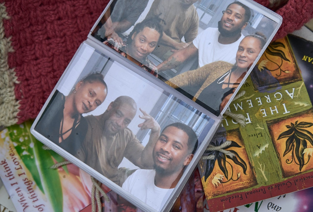 Shanyce Matthews wife of recently executed Terre Haute inmate, Orlando Hall poses for a portrait Monday, Dec. 21, 2020 in Milwaukee.  Shanyce displays some personal artifacts from her husbands last days along with family pictures and letters he wrote her the night before his execution. Shanyce holds up a photograph showing Eric Hampoton, left, Preisha Green , bottom left, and Orlando Hall Jr. right.  (Darren Hauck for The Intercept)