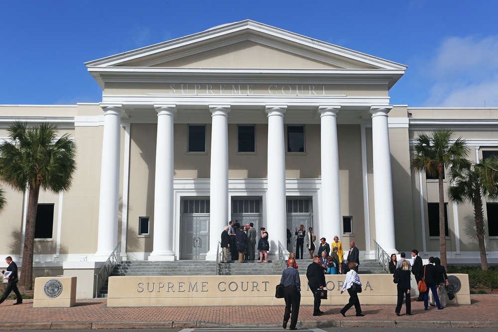FILE- In this March 4, 2015, file photo, people file into the Florida Supreme Court in Tallahassee, Fla. The Florida Supreme Court is ordering new sentencing hearings for four inmates currently on the state's death row. The high court on Thursday, June 29, 2017, threw out the sentences because a jury did not unanimously recommend the death penalty. (Scott Keeler/Tampa Bay Times via AP)