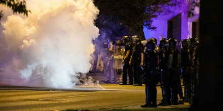 Police release tear gas at the intersection of Park and Academy Streets in Kalamazoo, Mich., early Tuesday, June 2, 2020, during protests against police brutality sparked by the death of George Floyd, a black man who died after being restrained by Minneapolis police officers on May 25.  The protests in Kalamazoo escalated into violence where several buildings and businesses were damaged. (Joel Bissell/Kalamazoo Gazette via AP)