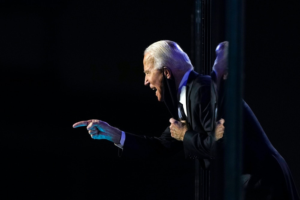 President-elect Joe Biden leans toward the cheering crowd, past the edge of protective glass on stage, on Saturday, Nov. 7, 2020, in Wilmington, Del. (AP Photo/Carolyn Kaster)