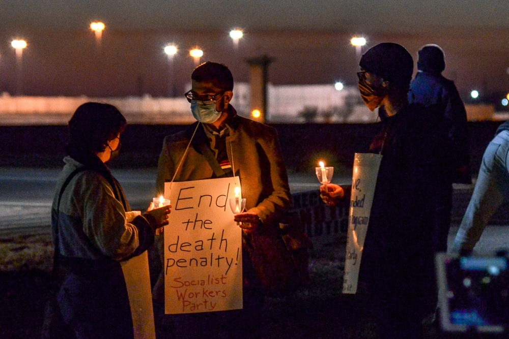 Gabby Prosser, left, and Nick Neeser, right, from Minneapolis, Minn., talk with Samir Hazboun, center, from Louisville, Ky., during a protest against the execution of Brandon Bernard across Prairieton Road from the Federal Death Chamber in Terre Haute, Ind., on Thursday evening, Dec. 10, 2020. (Austen Leake/The Tribune-Star via AP)