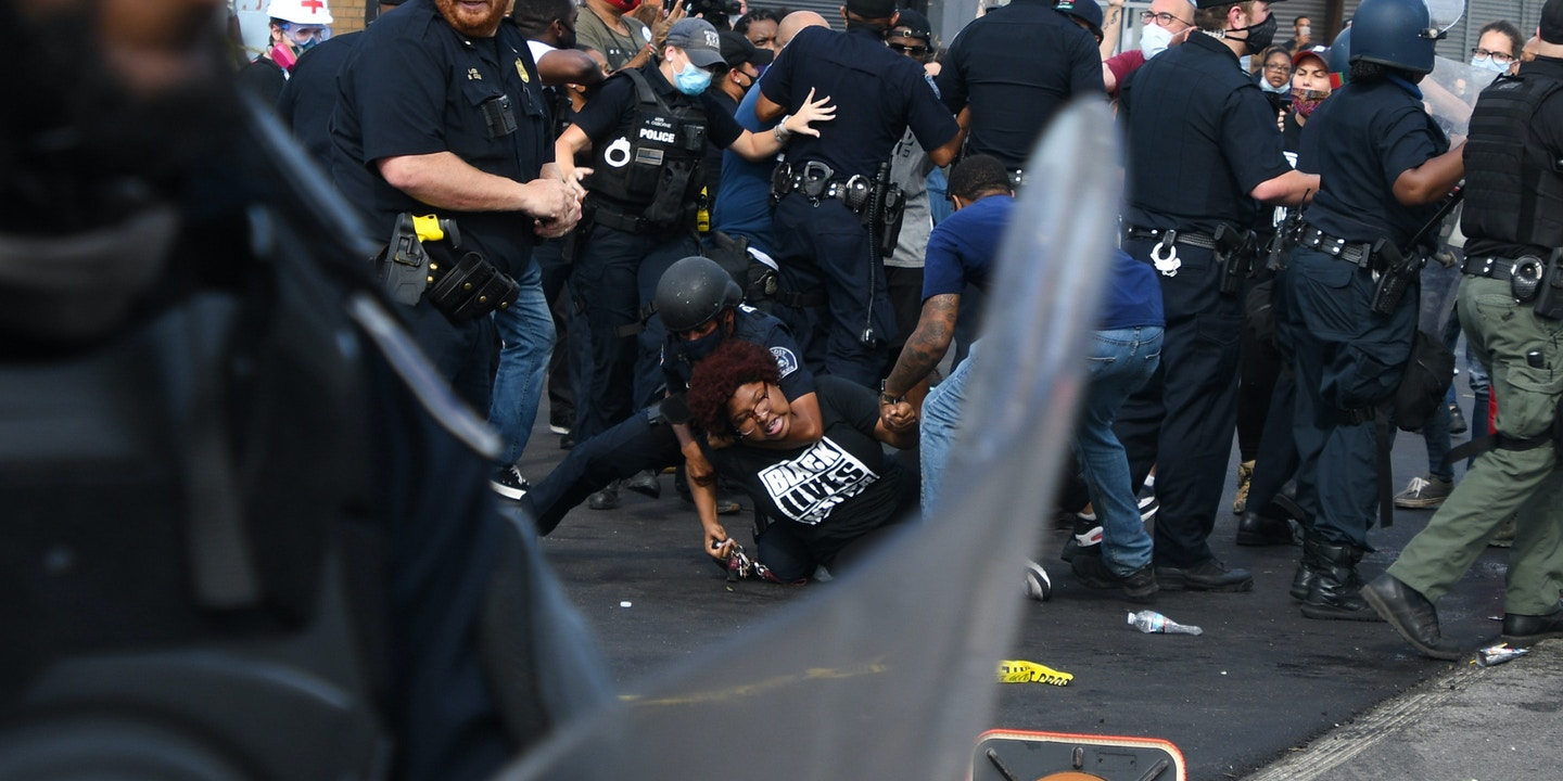 Organizer with the activist organization Detroit Will Breathe, Nakia Renne Wallace is placed into a chokehold by a Detroit police officer as riot police push into the crowd that organized in response to the police shooting of Hakim Littleton on July 10, 2020.