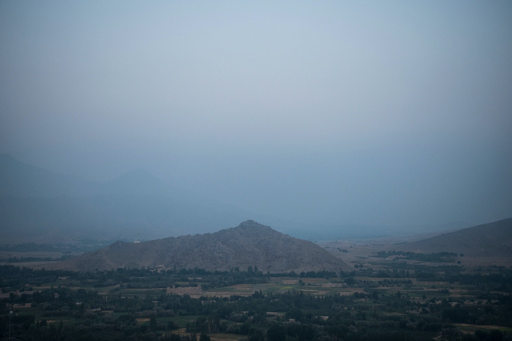 To either side of the hill lie the two entrances to the main valley of Wardak's Nerkh District, as viewed from a hilltop police checkpoint on the southern edge of Maidan Shahr, the capital of Wardak.