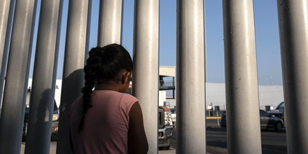 A Mexican girl who seeks for asylum in the US, looks through a fence at El Chaparral port of entry in Tijuana, Baja California state, Mexico on August 10, 2018, as she and her mother line up to cross to United States. - From the south border with Guatemala to the north border with the United States, AFP met during 24 hours migrants in pursue of their