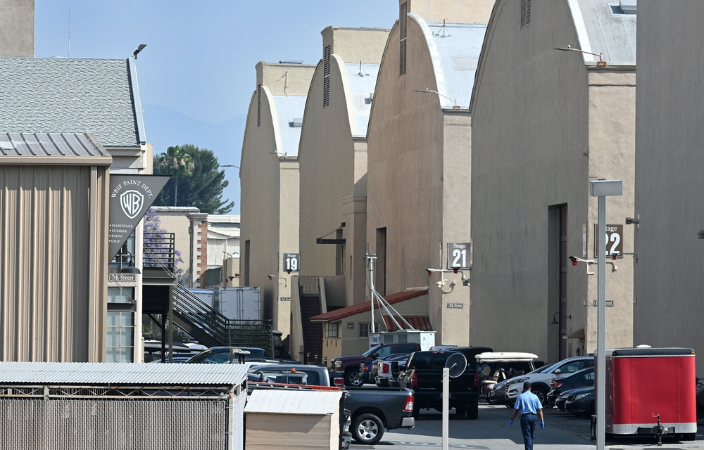 An employee walks by the filming stages at Warner Bros Studios in Burbank California on June 12, 2020. - The state of California has said film and television production can resume on June 12 after being shuttered since the Covid-19 pandemic stay-at-home order began. (Photo by Robyn Beck / AFP) (Photo by ROBYN BECK/AFP via Getty Images)