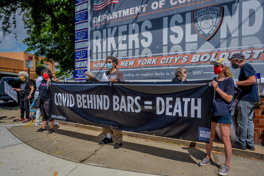 Participants holding a banner reading COVID BEHIND BARS = DEATH at the rally in Rikers Island on June 19, 2020.