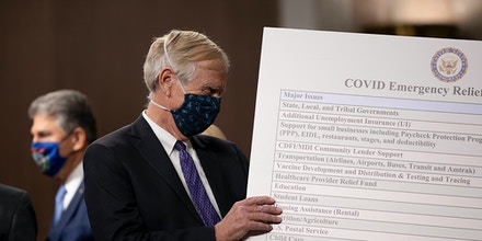 WASHINGTON, DC - DECEMBER 01: Sen. Angus King (I-ME) sets up a sign  alongside a bipartisan group of Democrat and Republican members of Congress as they announce a proposal for a Covid-19 relief bill on Capitol Hill on December 01, 2020 in Washington, DC. The roughly $908 billion proposal includes $288 billion in small business aid such as Paycheck Protection Program loans, $160 billion in state and local government relief and $180 billion to fund a $300 per week supplemental unemployment benefit through March, according to a draft framework. (Photo by Tasos Katopodis/Getty Images)