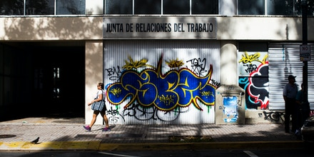 SAN JUAN, PUERTO RICO - NOVEMBER 12:  A woman walks past a vacant building on November 12, 2013 in the Santurce neighborhood of San Juan, Puerto Rico. The island territory of the United States, Puerto Rico, is on the brink of a debt crisis as lending has skyrocketed in the last decade as the government has been issuing municipal bonds. Market analysts have rated those bonds as junk and suspect it's 70 billion dollar debt might be unserviceable in the near future. With no industry other than tourism and the recent collapse of the real estate market, the way out is unclear. (Photo by Christopher Gregory/Getty Images)