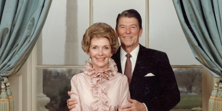 circa 1985:  Portrait of U. S. President Ronald Reagan, wearing a brown tie, standing behind First Lady Nancy Reagan, wearing a pink ruffled blouse and gathered red skirt in the Oval Office of the White House, Washington, D. C.  (Photo by Hulton Archive/Getty Images)