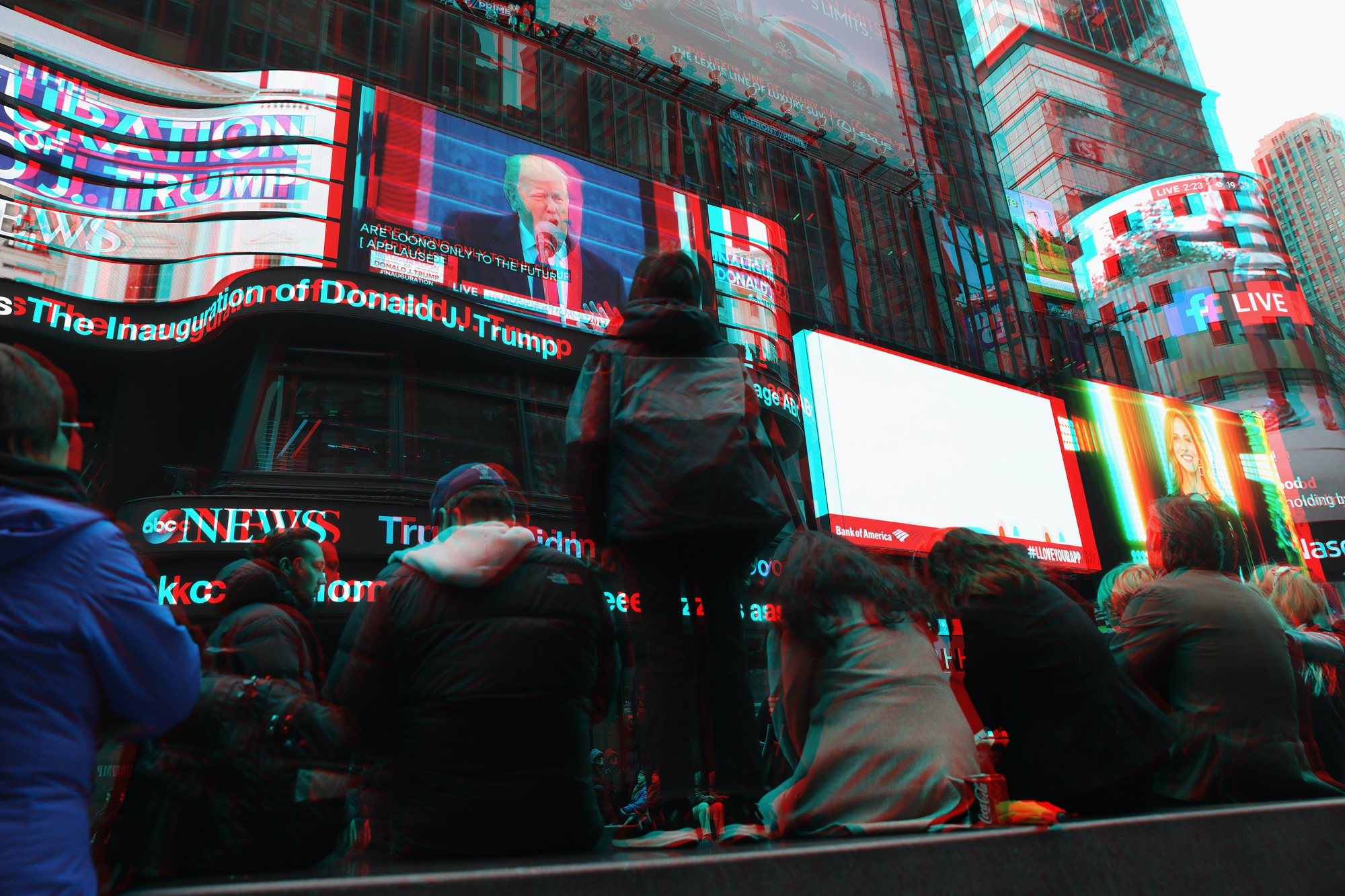 People watch the televised inauguration of Donald Trump as the 45th President of the United States while in Times Square on January 20, 2017 in New York City.