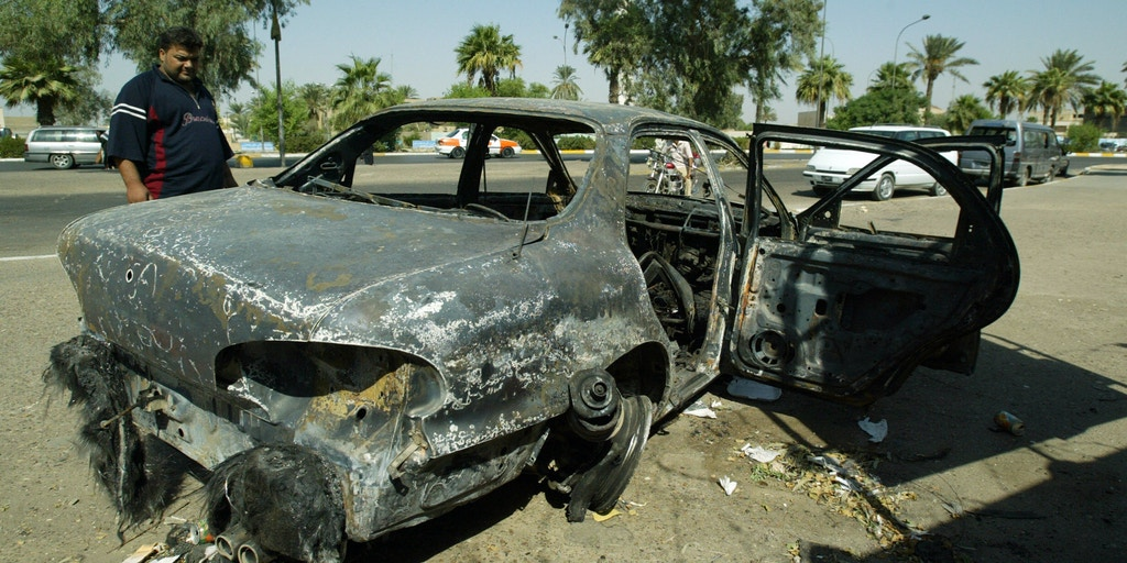 An Iraqi looks at a burnt car on the site where Blackwater guards who were escorting US embassy officials opened fire in the western Baghdad neighborhood of Yarmukh on September 24, 2007.