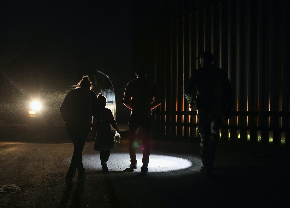 PENITAS, TX - FEBRUARY 22:  A Honduran mother walks with her children next to the U.S.-Mexico border fence as they turned themselves in to Border Patrol agents on February 22, 2018 near Penitas, Texas. Thousands of Central American families continue to enter the U.S., most seeking political asylum from violence in their home countries. The Rio Grande Valley has the highest number of undocumented immigrant crossings and narcotics smuggling of the entire U.S.-Mexico border.  (Photo by John Moore/Getty Images)