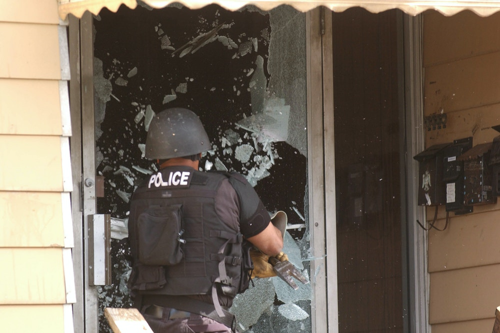 A Buffalo Police SWAT Team and Narcotics unit raided a series of homes in the city April 20, 2006. At a raid at 427 Grant St., Martin Motley smashes through the front glass door. (Bill Wippert/ Buffalo News/Rapport Syndication) (Bill Wippert/ Rapport Press)  (Newscom TagID: rsphotos008306.jpg) [Photo via Newscom]