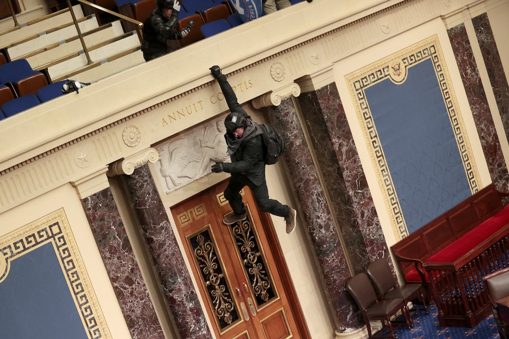 WASHINGTON, DC - JANUARY 06: A protester is seen hanging from the balcony in the Senate Chamber on January 06, 2021 in Washington, DC. Congress held a joint session today to ratify President-elect Joe Biden's 306-232 Electoral College win over President Donald Trump. Pro-Trump protesters have entered the U.S Capitol building after mass demonstrations in the nation's capital. (Photo by Win McNamee/Getty Images)