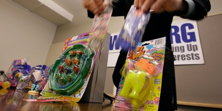 Blair Anundson displays toys that could be hazardous to children at a news conference by the organization where it released it's annual toy safety report Tuesday, Nov. 25, 2008, in Seattle. He was holding toys that contained high amounts of lead, setting them next to a