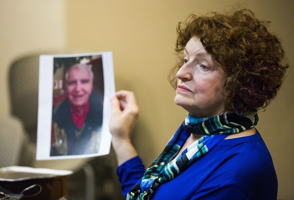 Witness Maryanne Tribble holds a photo of her father, John Snyder, who died of Legionnaire's disease in 2015, during the preliminary examination of Dr. Eden Wells, chief medical executive of the Michigan Department of Health and Human Services, on Monday, Nov. 6, 2017, in Genesee County District Court in downtown Flint, Mich. Wells faces charges of manslaughter, obstructing justice, lying to an investigator and misconduct in office in connection with her handling of the Flint water crisis. The water crisis has been linked to lethal outbreaks of Legionnaire's disease in Flint in 2014 and 2015. (Terray Sylvester/The Flint Journal-MLive.com via AP)