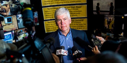FILE - In this Monday, June 6, 2016 file photo, journalists surround around Gov. Rick Snyder to ask him questions about the Flint water crisis after he toured skilled trades programs at Mott Community College in Flint, Mich. Flint had one of the worst man-made environmental debacles in U.S. history. Lead infected the distribution system in the city of 100,000, which was under the thumb of financial managers appointed by Snyder. Officials finally took action after a doctor reported high levels of lead in children. (Jake May/The Flint Journal - MLive.com via AP)