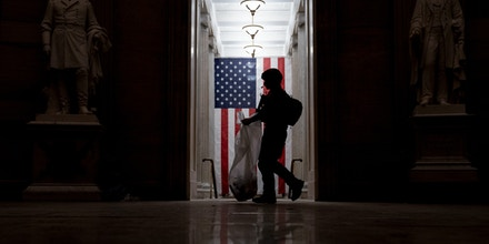 An ATF police officer cleans up debris across the floor of the Capitol Rotunda in the early morning hours after rioters stormed the building in Washington, D.C., on Jan. 7, 2021.