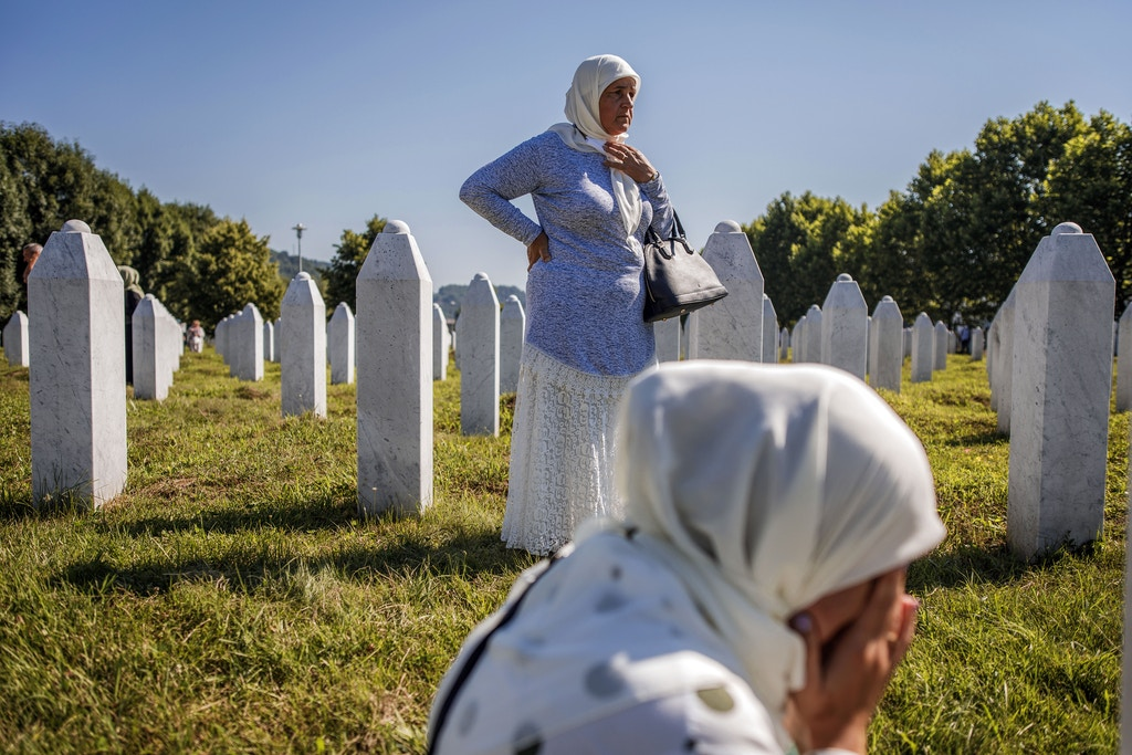 SREBRENICA, BOSNIA AND HERCEGOVINA - JULY 11: A Bosnian Muslim woman and her mother mourn by a grave of their father and husband on July 11, 2020 as newly identified victims are buried at the cemetery for victims of Srebrenica genocide in Potocari near Srebrenica, Bosnia and Hercegovina. More than 8,000 Bosnian Muslim men and boys were killed after the Bosnian Serb Army attacked Srebrenica, a designated UN safe area, on 10-11 July 1995, despite the presence of UN peacekeepers. There have been high-level prosecutions of some principal architects of the war in Bosnia and Herzegovina, including Ratko Mladic and Radovan Karadzic, yet there is still a backlog of cases pending before courts in the country. (Photo by Damir Sagolj/Getty Images)