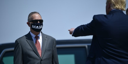US President Donald Trump shows the facial mask of  Representative Andy Biggs as he arrives to deliver remarks on immigration and border security at the international airport in Yuma, Arizona on August 18, 2020. (Photo by Brendan Smialowski / AFP) (Photo by BRENDAN SMIALOWSKI/AFP via Getty Images)