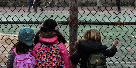 Children look at their school ground as they wait for class on the first day of school reopening on December 7, 2020 in the Brooklyn borough of New York City. - The novel coronavirus has killed at least 1,535,987 people since the outbreak emerged in China last December, according to a tally from official sources compiled by AFP at 1100 GMT on Monday. The US is the worst-affected country with 282,324 deaths. (Photo by Angela Weiss / AFP) (Photo by ANGELA WEISS/AFP via Getty Images)