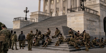 WASHINGTON, DC - JANUARY 11: National Guard eat breakfast while sitting on the steps to the House of Representatives on the U.S. Capitol Building grounds, as heightened security measures are in place nearly a week after a pro-Trump insurrectionist mob breached the security of the nations capitol while Congress voted to certify the 2020 Election Results on Monday, Jan. 11, 2021 in Washington, DC. (Kent Nishimura / Los Angeles Times via Getty Images)