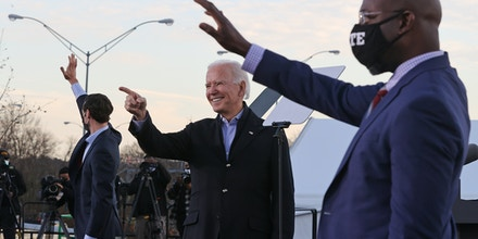 President-elect Joe Biden (C) rallys with Democratic candidates for the U.S. Senate Jon Ossoff (L) and Rev. Raphael Warnock (R) the day before their runoff election in the parking lot of Center Parc Stadium January 04, 2021 in Atlanta, Georgia.