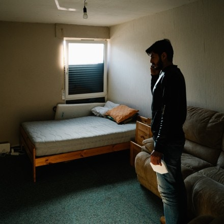 Fady in his apartment, calling his friend to meet. He pays 500€ for this one bedroom with a small kitchen. The blinds are broken.