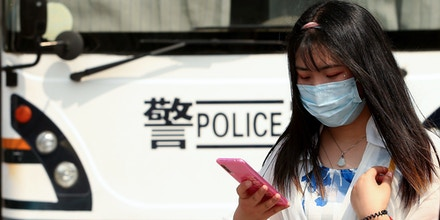 2BKHCMN Beijing, China. 04th May, 2020. A Chinese woman uses her phone next to a mobile police command bus as the government announced the Covid-19 threat is basically over in Beijing on Monday, May 4, 2020. China's capital lowered its emergency response to the novel coronavirus pandemic from the top level to the second level, the latest sign of social order restoration as the epidemic conditions have been eased, according to state media. Photo by Stephen Shaver/UPI Credit: UPI/Alamy Live News