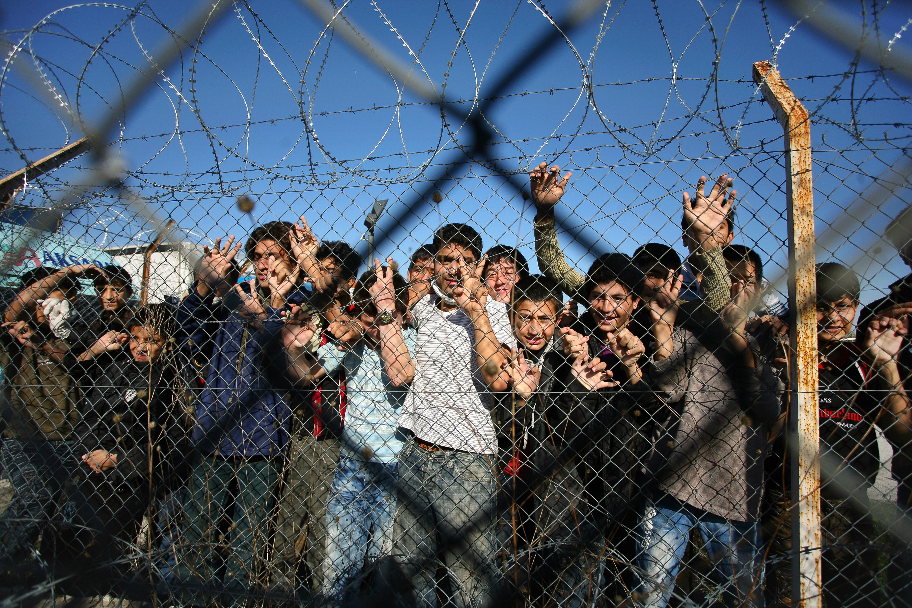 Immigrant minors peer out through the fence of an immigrant detention center in the village of Filakio, on the Greek-Turkish border, upon the arrival there of the Frontex Rapid Border Intervention Teams (RABITs) and EU officials on November 5, 2010. Border guards from 26 nations began arriving on November 2 in northeastern Greece to help curb a wave of illegal immigrants crossing over from Turkey, European border agency Frontex said. Coordinated by Greek police, some 170 guards will be on hand and until the end of December to monitor borders and scout for illegal immigrants, Frontex spokesman Michal Parzyszek said. AFP PHOTO /Sakis Mitrolidis (Photo credit should read SAKIS MITROLIDIS/AFP via Getty Images)