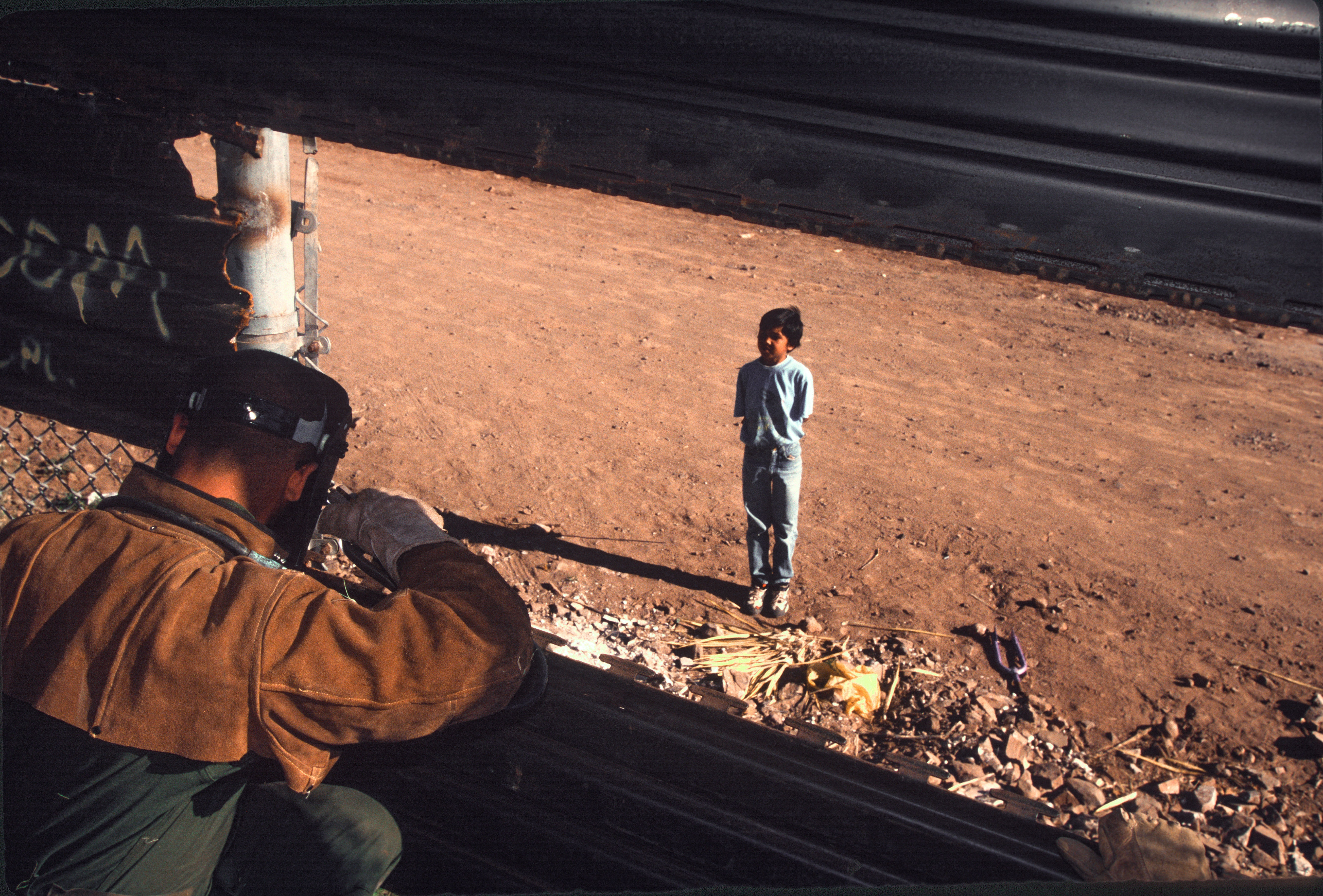 NOGALES, AZ - APRIL 10: United States army engineers extend a border wall as a Mexican boy on the other side watches on April 10, 1995 on the outskirts of Nogales, Arizona.(Photo by Andrew Lichtenstein/Corbis via Getty Images)