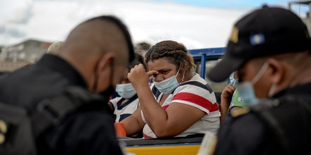 Honduran migrants who voluntarely return to their country get off a police truck in El Florido, Chiquimula, Guatemala on January 19, 2021, on the border with Honduras. - On buses and trucks, Guatemala transported Tuesday several groups of migrants who were part of a US-bound caravan back to Honduras, after police and military officers forced them to desist from the crossing. (Photo by Johan ORDONEZ / AFP) (Photo by JOHAN ORDONEZ/AFP via Getty Images)