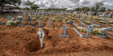 Worker wearing personal protective equipment (PPE) digs a grave at a cemetery in Manaus, Brazil, on Tuesday, Jan. 19, 2021. Severe oxygen shortages at hospitals in Brazil's Amazon prompted local authorities to impose a curfew and airlift patients to other states to deal with the onslaught of a second coronavirus wave. Photographer: Jonne Roriz/Bloomberg via Getty Images