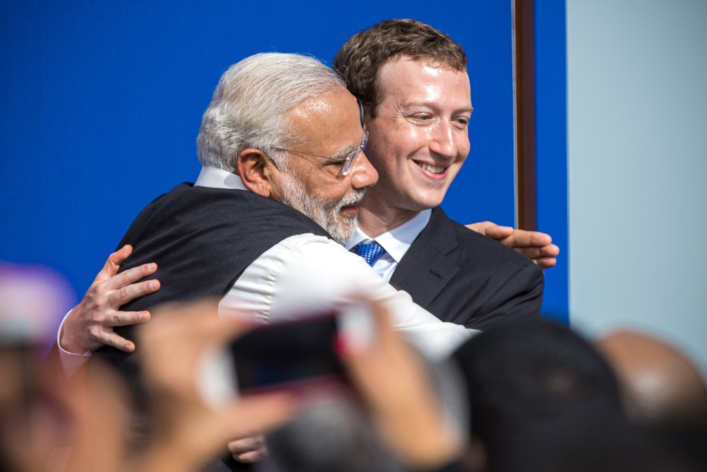 "Narendra Modi, India's prime minister, left, and Mark Zuckerberg, chief executive officer of Facebook Inc., embrace at the conclusion of a town hall meeting at Facebook headquarters in Menlo Park, California, U.S., on Sunday, Sept. 27, 2015. Prime Minister Modi plans on connecting 600,000 villages across India using fiber optic cable as part of his ""dream"" to expand the world's largest democracy's economy to $20 trillion. Photographer: David Paul Morris/Bloomberg via Getty Images"