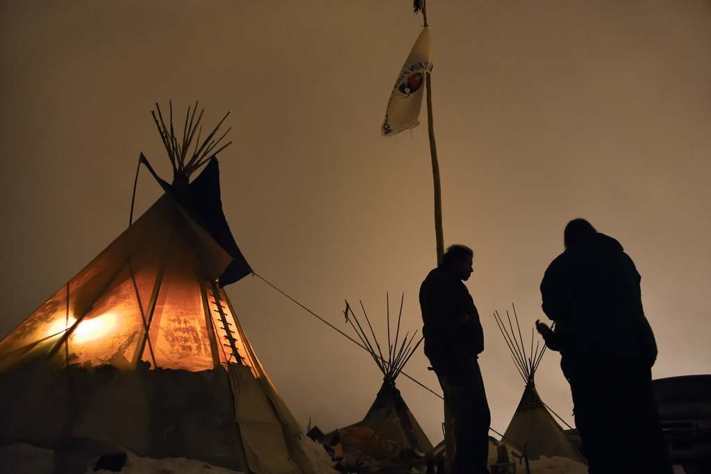 CANNON BALL, NORTH DAKOTA - DECEMBER 1: Matt Black Eagle Man, middle, a member of the Long Plain First Nation, chats with friends outside of his teepee at Oceti Sakowin Camp on the edge of the Standing Rock Sioux Reservation on Dec. 1, 2016 outside Cannon Ball, North Dakota. Native Americans and activists from around the country have been gathering at the camp for several months trying to halt the construction of the Dakota Access Pipeline. The proposed 1,172-mile-long pipeline would transport oil from the North Dakota Bakken region through South Dakota, Iowa and into Illinois. on December 1, 2016 in Cannon Ball North Dakota, Colorado.  (Photo by Helen H. Richardson/The Denver Post via Getty Images)