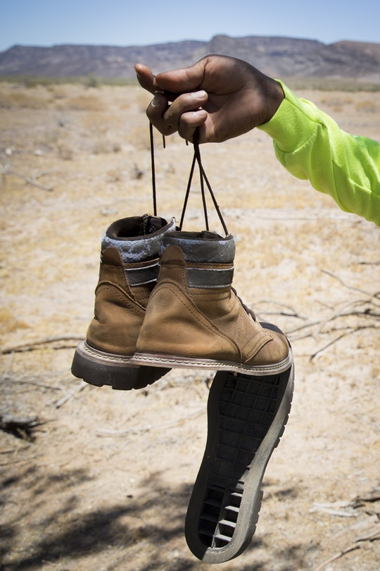 One of the soles of Gilberto Mateos's shoes hangs as the glue melted and came apart during a mission with Aguílas del Desierto search and rescue crew on May 27, 2017 in the Cabeza Prieta wilderness near Ajo, Arizona. (Photo by Caitlin O'Hara/Getty Images)