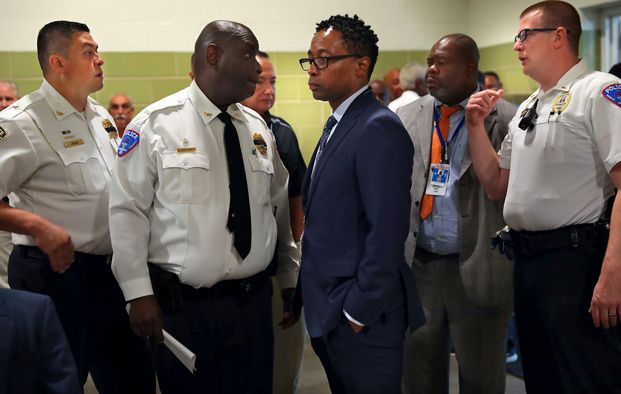 St. Louis County Prosecutor Wesley Bell, center, is surrounded by area police chiefs, on June 24, 2019.
