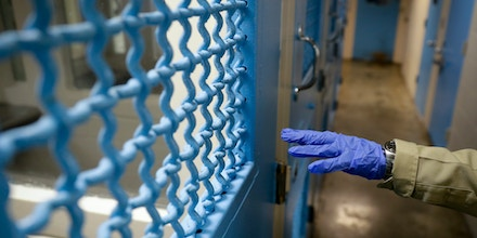 A gloved hand points to a holding cell at the hospital ward of the Twin Towers jail in Los Angeles on April 16, 2020.
