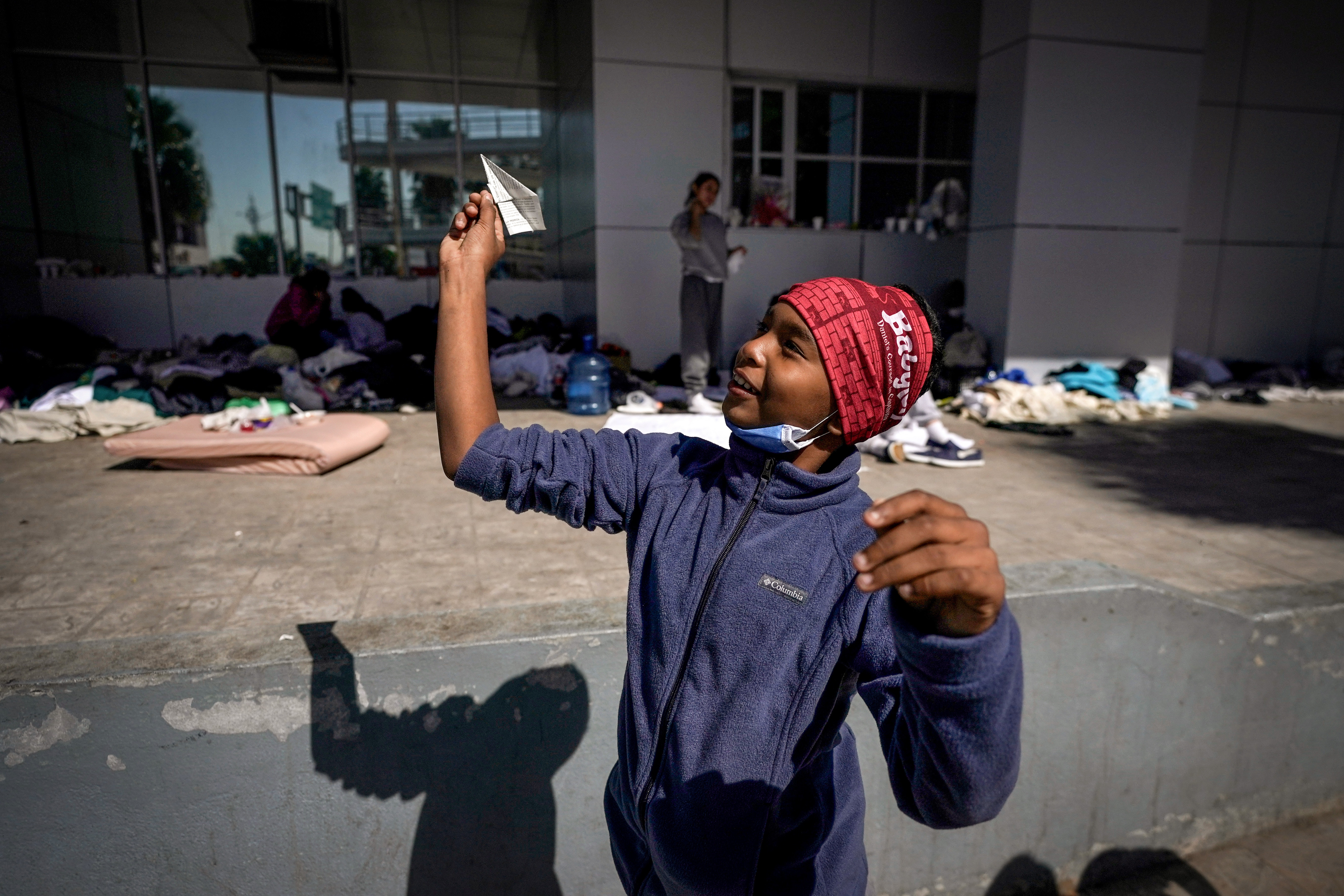 A migrant boy launches a paper airplane while playing with other migrant kids at a plaza near the McAllen-Hidalgo International Bridge point of entry into the United States after being caught trying to sneak into the U.S. and deported, Thursday, March 18, 2021, in Reynosa, Mexico. A surge of migrants on the Southwest border has the Biden administration on the defensive. The head of Homeland Security acknowledged the severity of the problem Tuesday but insisted it's under control and said he won't revive a Trump-era practice of immediately expelling teens and children. (AP Photo/Julio Cortez)
